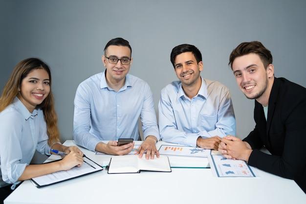 Retrato de equipe de negócios feliz sentado à mesa e sorrindo