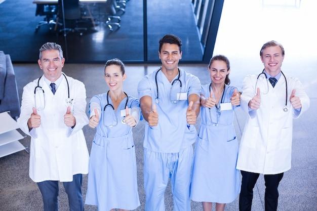 Retrato, de, equipe médica, colocar, seu, polegares cima, e, sorrindo