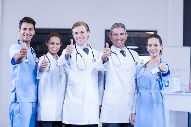 Retrato, de, equipe médica, pôr, polegares cima, e, sorrindo, em, hospitalar