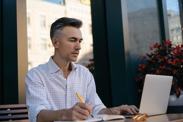 Retrato de escritor maduro bonito usando laptop, fazendo anotações no caderno