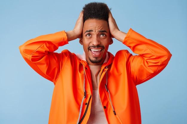 Retrato de espantado jovem afro-americano de pele escura numa capa de chuva laranja, segurando sua cabeça, parece louco e confuso com carrinhos de fracasso.