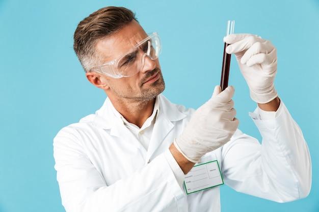 Retrato de especialista médico sério usando óculos segurando um tubo de ensaio com sangue, isolado sobre a parede azul