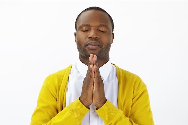 Retrato de esperançoso homem afro-americano adulto fechando os olhos e pressionando as palmas das mãos, orando, esperando pelo melhor. homem calmo e pacífico de pele escura de mãos dadas em namaste enquanto medita