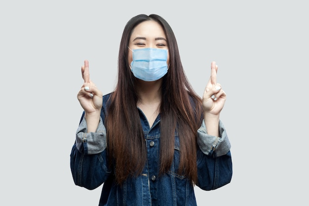Retrato de esperançoso morena jovem asiática com máscara médica cirúrgica em jaqueta jeans azul em pé com o dedo cruzado e rezando para ganhar. tiro de estúdio interno, isolado em fundo cinza.