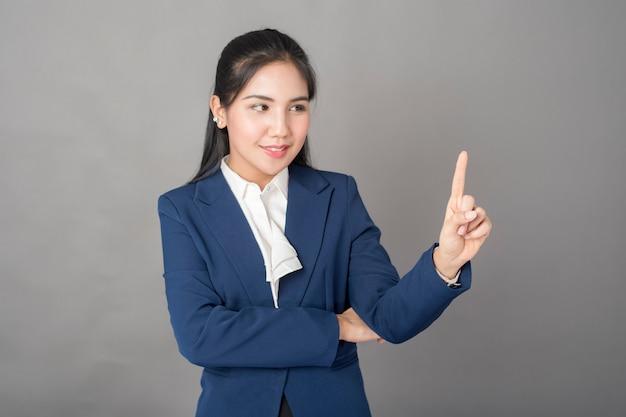 Retrato, de, esperto, mulher negócio, em, terno azul, ligado, experiência cinza, tiro estúdio