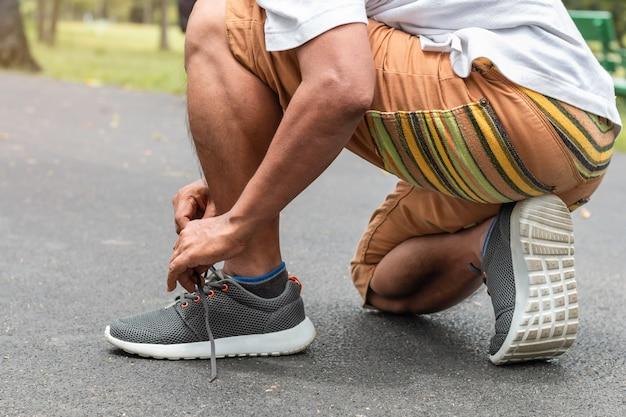 Retrato de esportes asiáticos sênior homem amarrar cadarços na estrada.