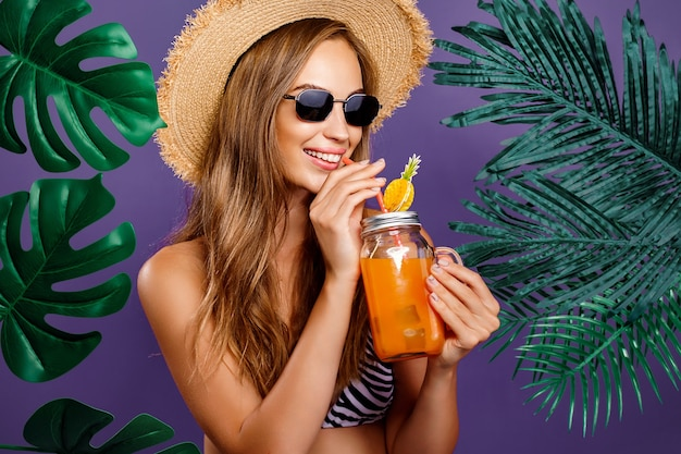 Retrato de estilo de verão de jovem atraente usando óculos escuros bebendo coquetel