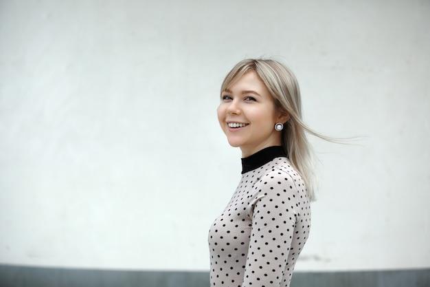 Retrato de estilo de vida ao ar livre de feliz garota loira deslumbrante. caminhando para a rua da cidade.