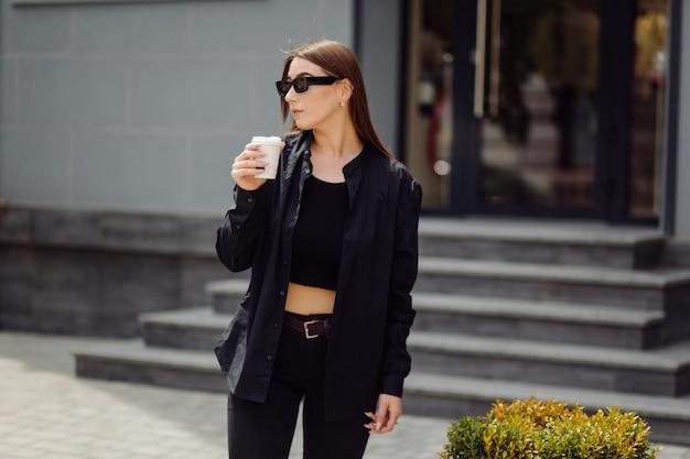 Retrato de estilo de vida ao ar livre de uma deslumbrante menina morena. beber café e andar pelas ruas da cidade.