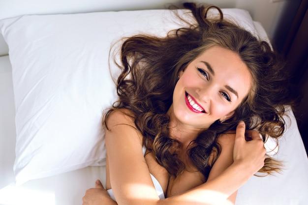 Retrato de estilo de vida de moda interior de jovem fresco incrível mulher posando na cama, vestindo lingerie sedutora, relaxando e se divertindo pela manhã.