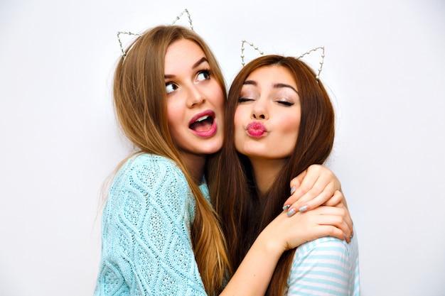 Retrato de estilo de vida de moda interior de mulheres de amigos muito felizes, abraços, vestindo suéteres de cashmere pastel aconchegantes com menta, cabelos castanhos e loiros, maquiagem, acessório da moda, enviando beijo no ar.