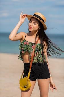 Retrato de estilo de vida de verão ao ar livre de ajuste mulher sorridente com corpo se divertindo na praia tropical usando chapéu de palha.