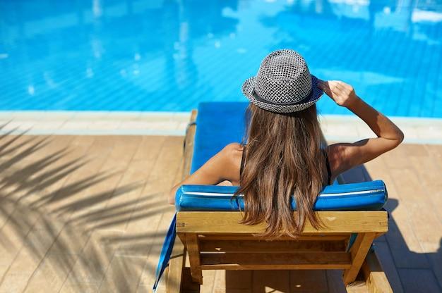 Retrato de estilo de vida de verão da mulher jovem e bonita bronzeada em um chapéu perto da piscina