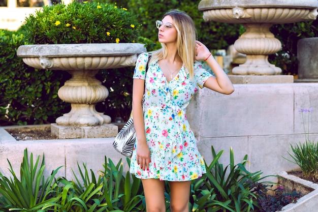 Retrato de estilo de vida de verão de feliz magnífica loira elegante mulher usando vestido de chá floral na moda elegante luz e posando no antigo parque europeu, clima de viagem.
