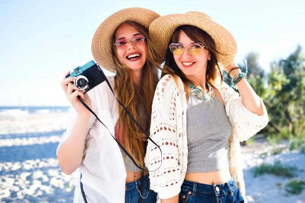 Retrato de estilo de vida de verão de meninas de irmã melhores amigos felizes posando na praia, cores claras de sol, chapéus de palha e óculos escuros, segurando a câmera fotográfica vintage, se divertindo juntos.