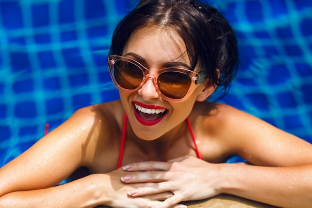 Retrato de estilo de vida de verão de mulher de beleza deslumbrante sexy nadando na piscina, tomando banho de sol e relaxar, férias de luxo.