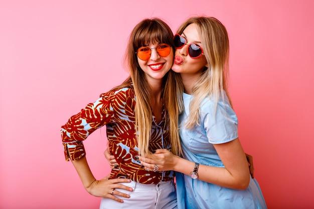 Retrato de estilo de vida feliz, lindas, duas melhores amigas, irmãs, posando e se divertindo juntas na parede rosa