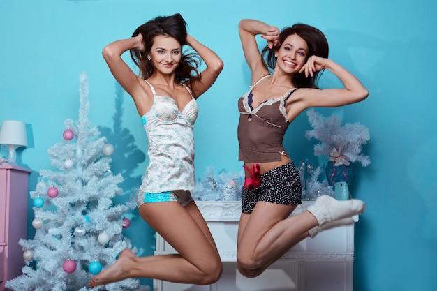 Retrato de estilo de vida interior de duas garotas loucas hipster de melhores amigos