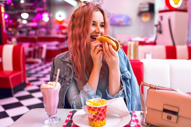 Retrato de estilo de vida positivo de mulher bonita feliz saiu com cabelos rosa jantando no café americano vintage, comendo cachorro-quente, batata frita e mil shake, refeição de trapaça de junk food, cores pastel.