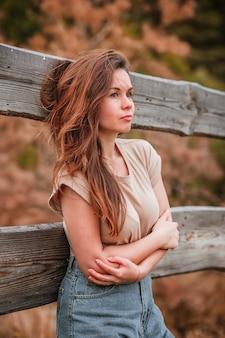 Retrato de estilo rural de uma jovem encostada a uma cerca de madeira na aldeia no início do outono