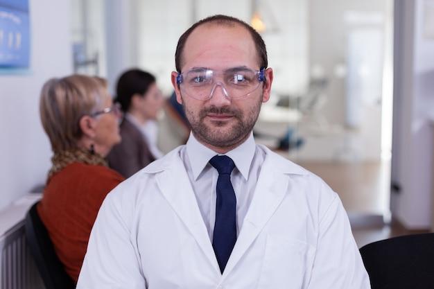 Retrato de estomatologista sorrindo para a câmera no consultório odontológico enquanto os pacientes esperam por ele no fundo