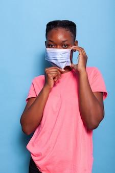 Retrato de estudante afro-americano colocando máscara de proteção médica