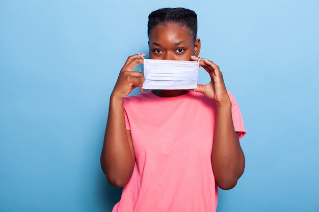 Retrato de estudante afro-americano colocando máscara protetora médica