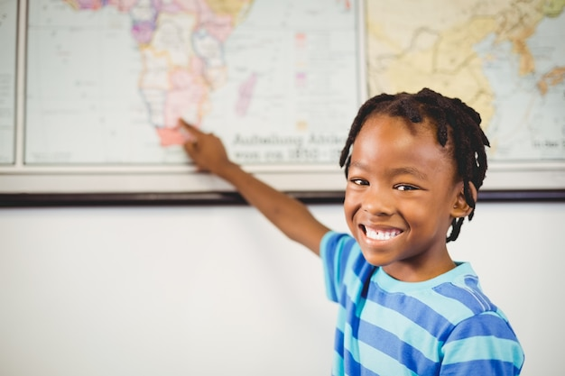Retrato de estudante apontando no mapa na sala de aula