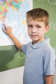 Retrato de estudante, apontando para o mapa na sala de aula