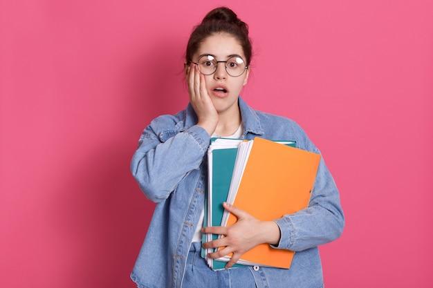 Retrato de estudante com coque de cabelo, usa jeans e óculos arredondados, segurando pastas de papel colorido