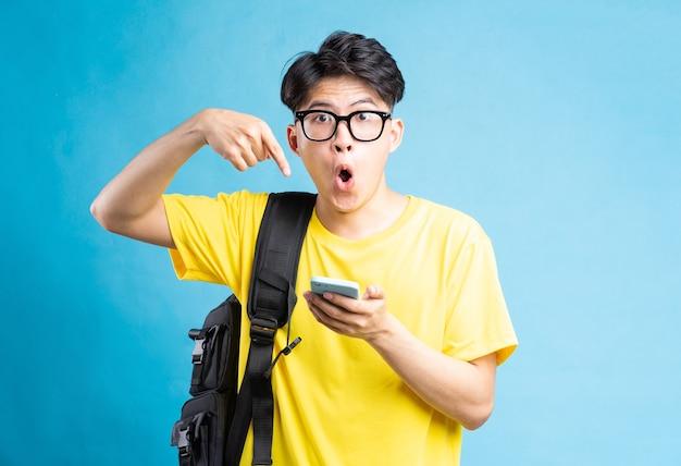 Retrato de estudante do sexo masculino apontando para smartphone com expressão de surpresa, isolado em um fundo azul