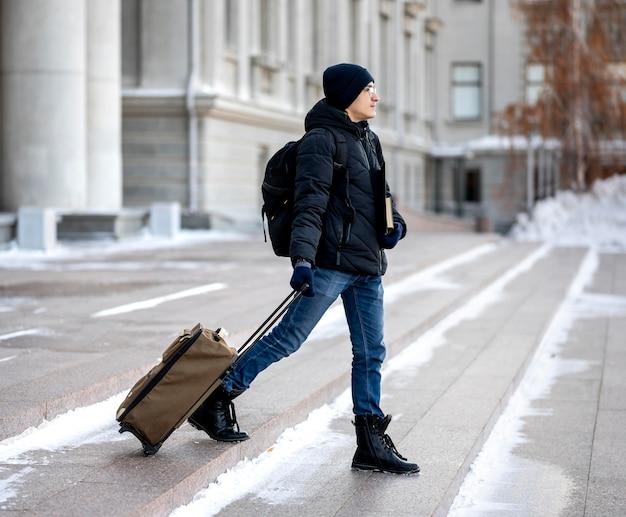Retrato de estudante do sexo masculino com livros e bagagem