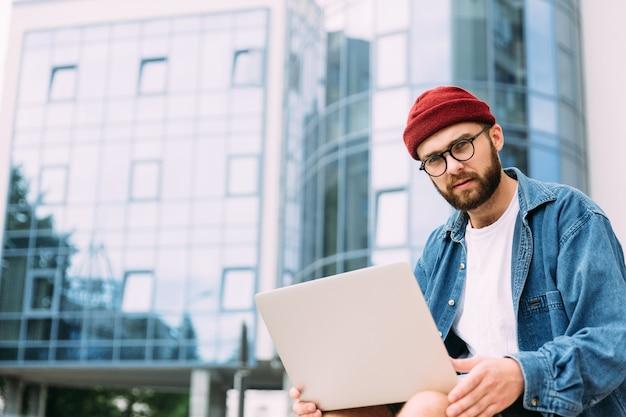 Retrato de estudante do sexo masculino hipster barbudo bonito em espetáculos, olhando diretamente para a câmera. espaço para texto.