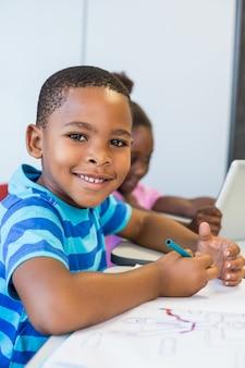 Retrato de estudante fazendo lição de casa em sala de aula
