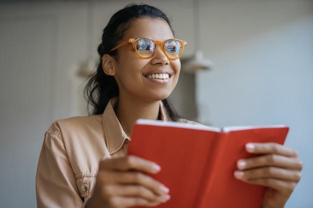 Retrato de estudante feliz em óculos elegantes, estudando, aprendendo línguas, lendo um livro, preparação para o exame, conceito de educação