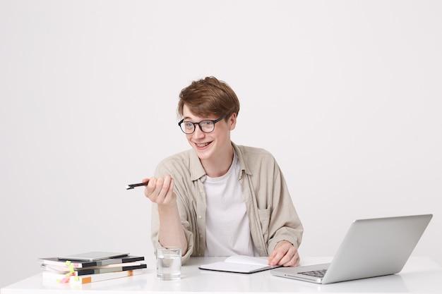 Retrato de estudante jovem atraente e alegre usa óculos e a camisa bege aponta para o lado e estuda na mesa com o laptop e notebooks isolados sobre a parede branca