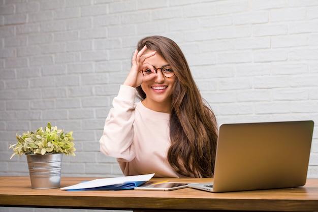 Retrato, de, estudante jovem, latim, mulher senta-se, ligado, dela, escrivaninha, alegre, e, confiante, fazendo, ok