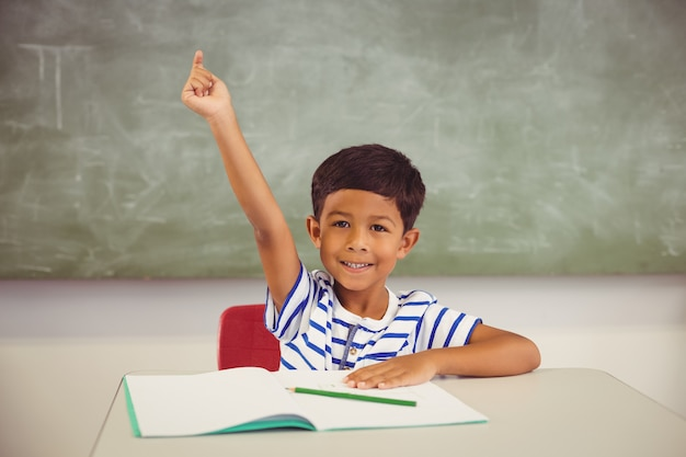 Retrato de estudante, levantando a mão na sala de aula