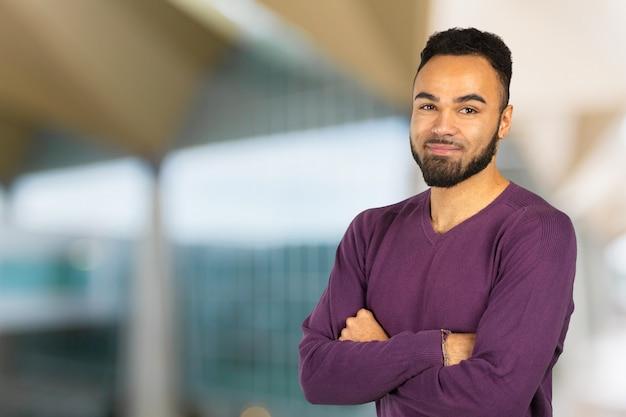 Retrato de estudante masculino africano stong e bonito, olhando para a câmera sorrindo