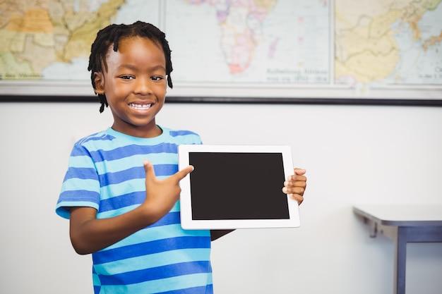 Retrato de estudante mostrando tablet digital em sala de aula