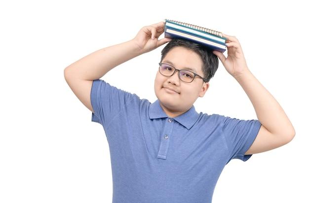 Retrato de estudante obeso segurando um livro acima de sua cabeça. fundo isolado. educação e volta ao conceito de escola.