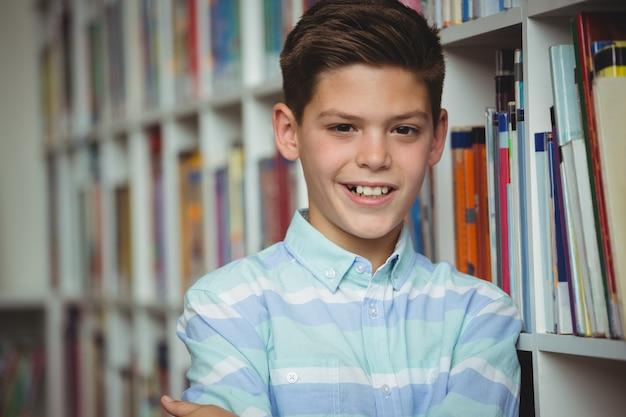 Retrato de estudante sorridente em pé com os braços cruzados na biblioteca