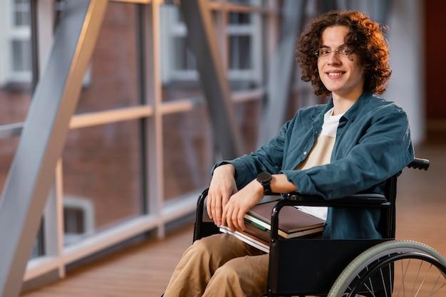 Retrato de estudante sorridente em uma cadeira de rodas