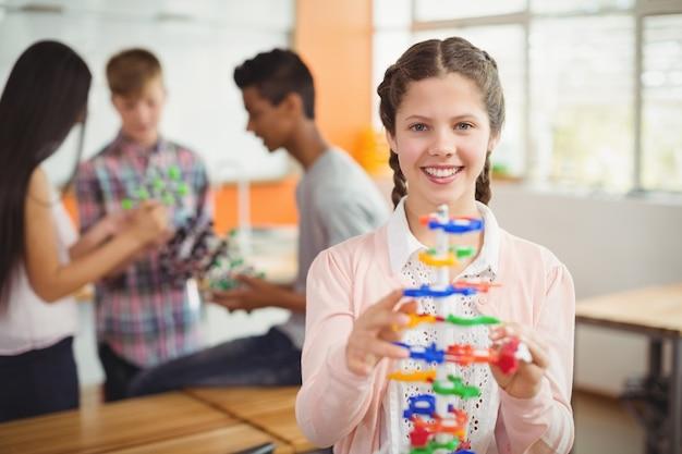 Retrato de estudante sorridente examinando o modelo da molécula em laboratório