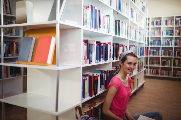 Retrato de estudante sorridente na biblioteca