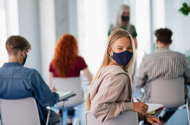 Retrato de estudante universitário em sala de aula dentro de casa, coronavírus e de volta ao conceito normal.