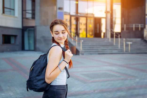 Retrato de estudante universitário, menina com mochila ao ir para a faculdade de rua, adolescente no campus. conceito de educação