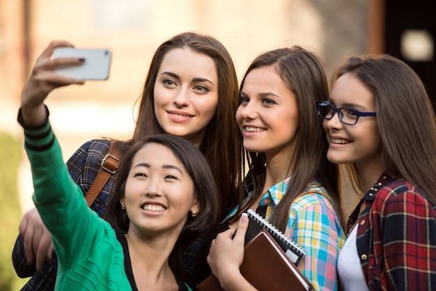Retrato de estudantes do sexo feminino que estão fazendo fotos.