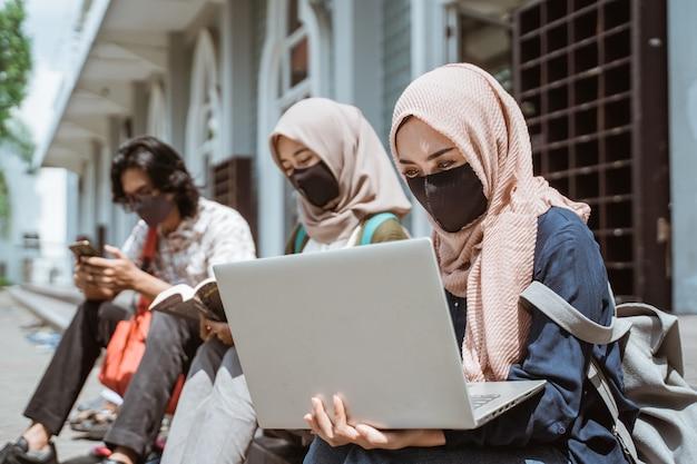 Retrato de estudantes muçulmanas usando máscaras e ocupadas fazendo suas tarefas em um laptop