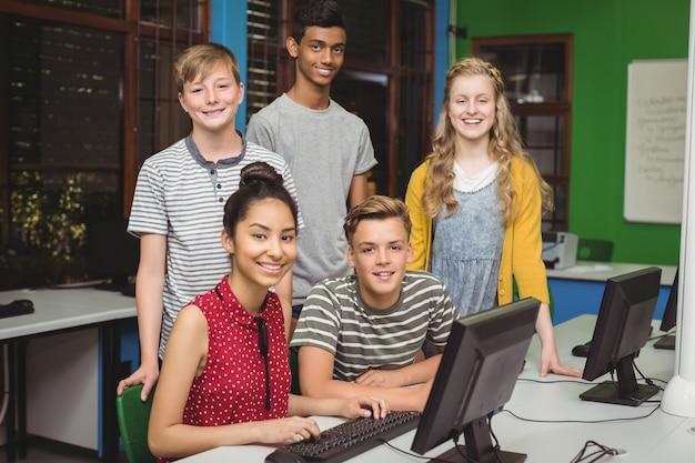 Retrato de estudantes sorridentes em uma sala de aula de informática